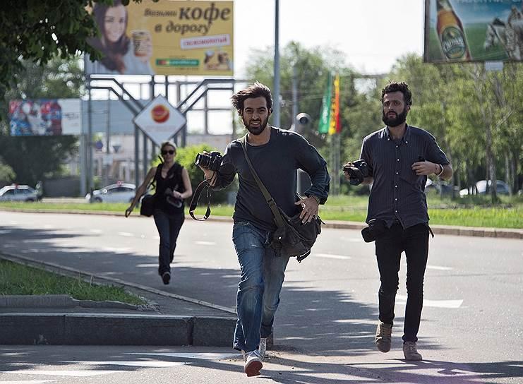 26 мая. Журналисты убегают во время обстрела в районе аэропорта Донецка