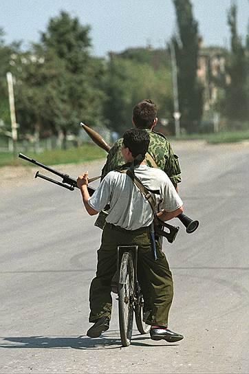 1995 год. Вооруженные автоматами чеченские дети едут на велосипеде по улице города