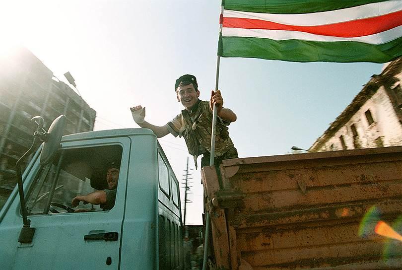 1995 год. Мужчина в кузове грузовика держит развивающийся чеченский флаг в первые дни после повторного взятия Грозного боевиками