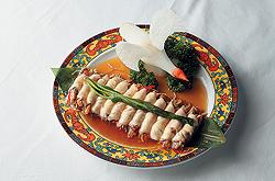 """В """"Джун Го"""" из сибаса готовят рулеты, начиняют их грибами, подают на темном бамбуковом листе и украшают белой птицей, вырезанной из дайкона"""