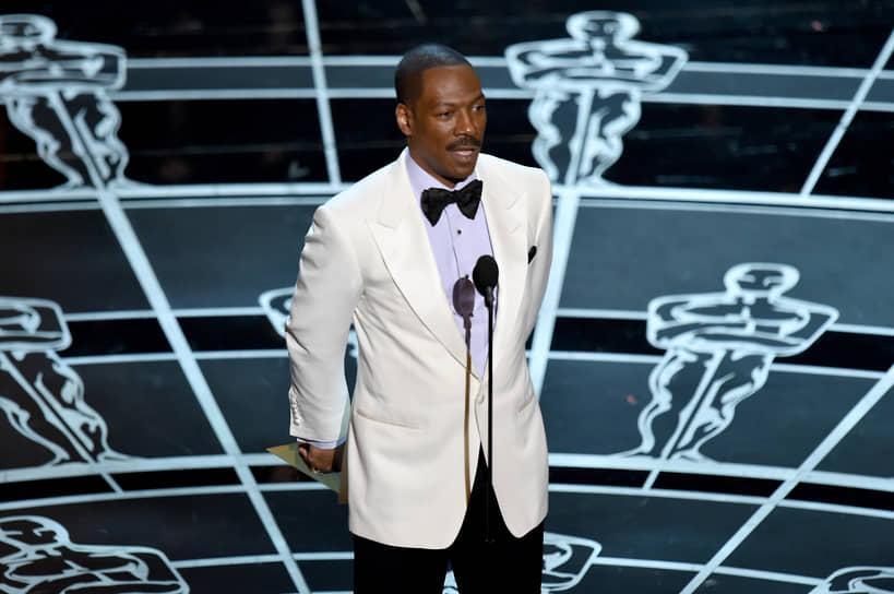 За свою актерскую карьеру Мерфи снялся в более чем 40 фильмах. В 2019 году, спустя 35 лет, Мерфи вернулся в эфир комедийной телепередачи «Субботним вечером в прямом эфире» на телеканале NBC, став ведущим рождественского выпуска программы, которая в свое время сделала его популярным  <br>На фото: Эдди Мерфи в роли ведущего на церемонии вручения премии «Оскар» в 2015 году