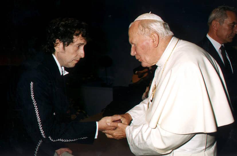 В 1997 году после продолжительной болезни, о которой сам Дилан говорил, что «приготовился увидеть Элвиса», музыкант совершил путешествие в Болонью, где папа Иоанн Павел II произнес проповедь, основанную на темах дилановского гимна 60-х «Blowin' In The Wind». Позднее музыкант неоднократно встречался с понтификом<br>На фото: Боб Дилан и Иоанн Павел II, 2003 год
