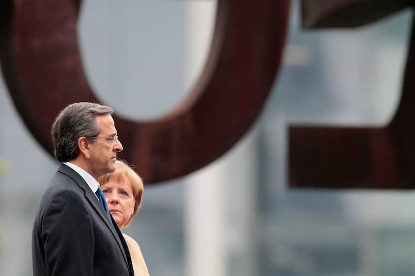 Среди непопулярных у населения инициатив Меркель — спасение столкнувшихся с финансовыми трудностями стран Евросоюза. Именно благодаря ей Греция в 2012 году получила дополнительную помощь в размере €130 млрд<br>На фото: Ангела Меркель и бывший премьер-министр Греции Антонис Самарас