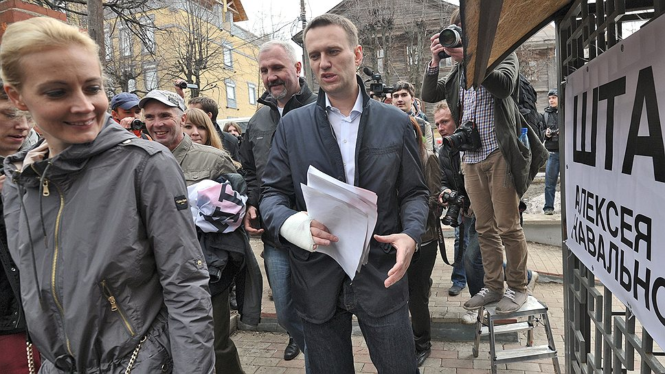 Председатель Координационного совета оппозиции Алексей Навальный (в центре) с супругой Юлией (слева) по дороге в штаб сторонников Алексея Навального, 2013 год