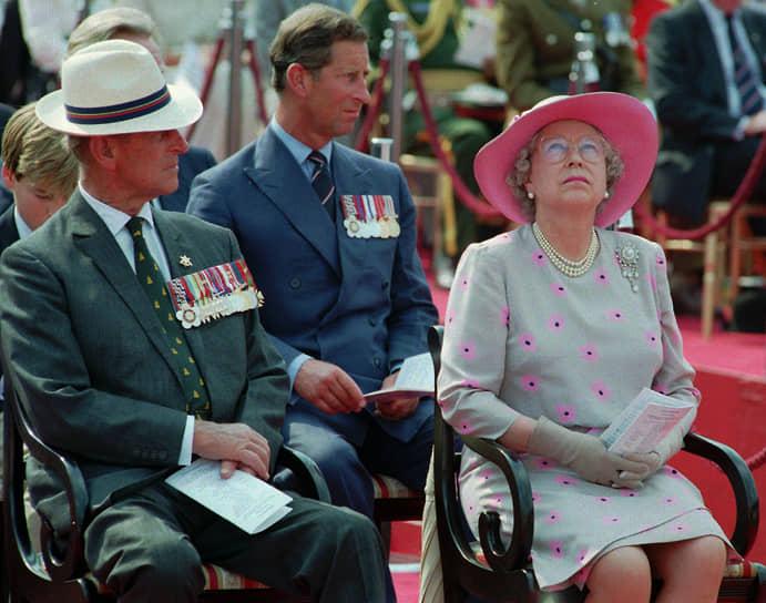 На фото слева направо: принц Филипп, принц Чарльз и королева Елизавета II на мероприятии по случаю празднования победы над Японией во Второй мировой войне в августе 1995 года