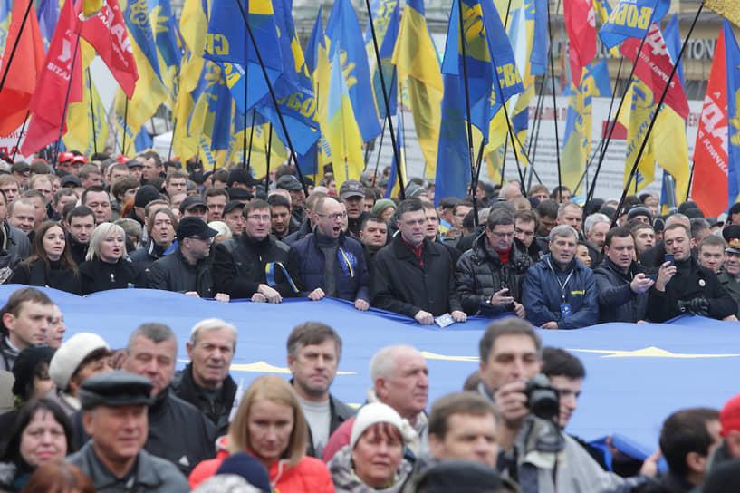 Остановка процесса евроинтеграции привела в конце ноября 2013 года к массовым протестам на Майдане<br> На фото cлева направо за баннером: дочь Юлии Тимошенко Евгения, член «Батькивщины» Ирина Луценко, бывший министр внутренних дел Украины Юрий Луценко и другие представители оппозиционных сил
