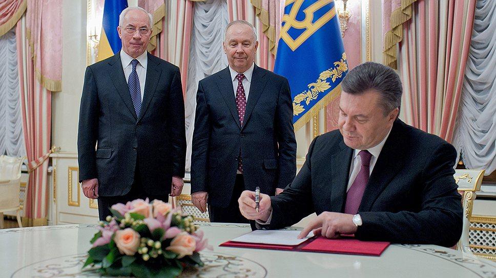 Президент Украины Виктор Янукович (справа) во время подписания указа о назначении Николая Азарова (слева) премьер-министром Украины. В центре председатель Верховной рады Украины VII созыва Владимир Рыбак (13 декабря 2012 года)