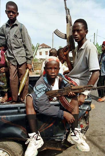 Африка — лидер по числу воюющих детей: по некоторым оценкам, в зонах конфликтов в центральной и западной части континента солдатом является каждый десятый ребенок<br> На фото: бойцы Национально-патриотического фронта Либерии на улицах столицы страны — Монровии