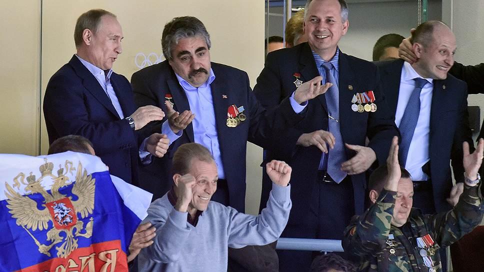 Президент России Владимир Путин (слева) с ветеранами войны в Афганистане во время матча группового этапа по хоккею между сборными России и США