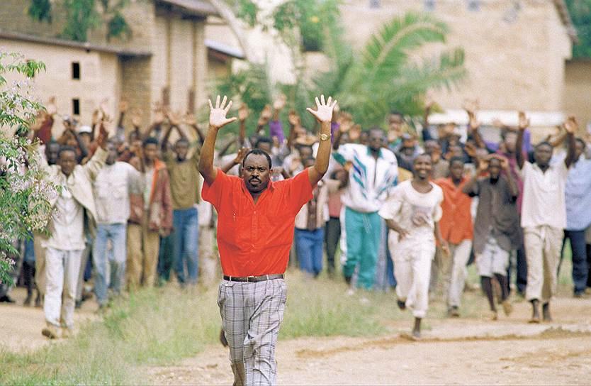 В то время когда Руанда была бельгийской колонией, метрополия сознательно разделяла ее жителей: представители тутси считались элитой и получали лучшие рабочие места и разные привилегии. После получения Руандой независимости в 1962 году ситуация кардинально поменялась: угнетенное большинство, хуту, воспрянуло и стало притеснять тутси. РПФ, который возглавлял Поль Кагаме, в начале 1990-х вел борьбу против правительства хуту<br> На фото: пациенты психиатрической больницы в районе Кигали просят о помощи бельгийских солдат