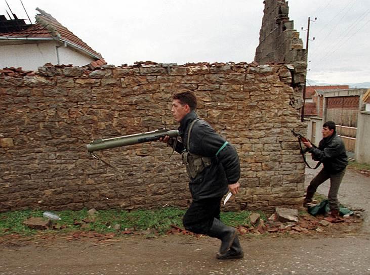 10 июня Сербия согласилась вывести войска из Косово. В регион ввели KFOR — международные миротворческие силы под эгидой НАТО. Однако первыми на территорию Косово вошли российские десантники, совершив из Боснии «бросок на Приштину» (в 2003 году российские миротворцы покинули регион)<br>На фото: солдаты Освободительной армии Косово в пригороде Приштины, 21 февраля 1999 года