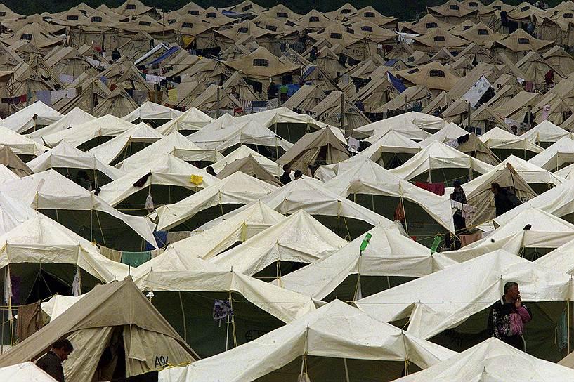 В 2004 году ситуация в Косово вновь резко обострилась. Там произошли кровопролитные столкновения между албанцами и сербами — самые крупные с момента окончания войны 1999 года. Поводом для столкновений послужила гибель трех албанских подростков, которые накануне утонули в Ибре. Албанские СМИ тут же сообщили, что подростков в реку загнали сербские дети из соседнего села. Очень быстро беспорядки распространились почти на все Косово. Они показали, что до решения едва ли не самой острой проблемы в Европе еще далеко<br>На фото: лагерь беженцев в Чегране, Македония, 7 мая 1999 года