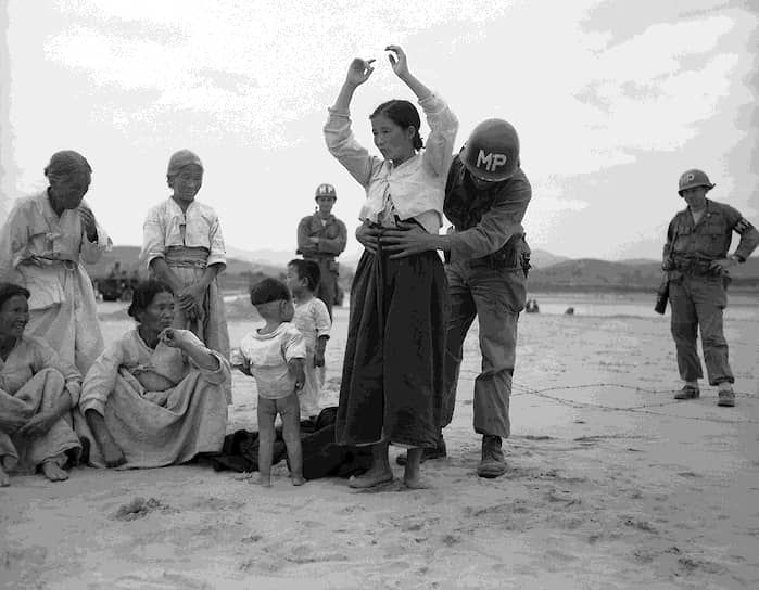 Известны случаи, когда мирных женщин заставляли переправлять оружие и боеприпасы для солдат северокорейской армии<br> На фото: американские военные обыскивают женщин, подозреваемых в пособничестве армии КНДР