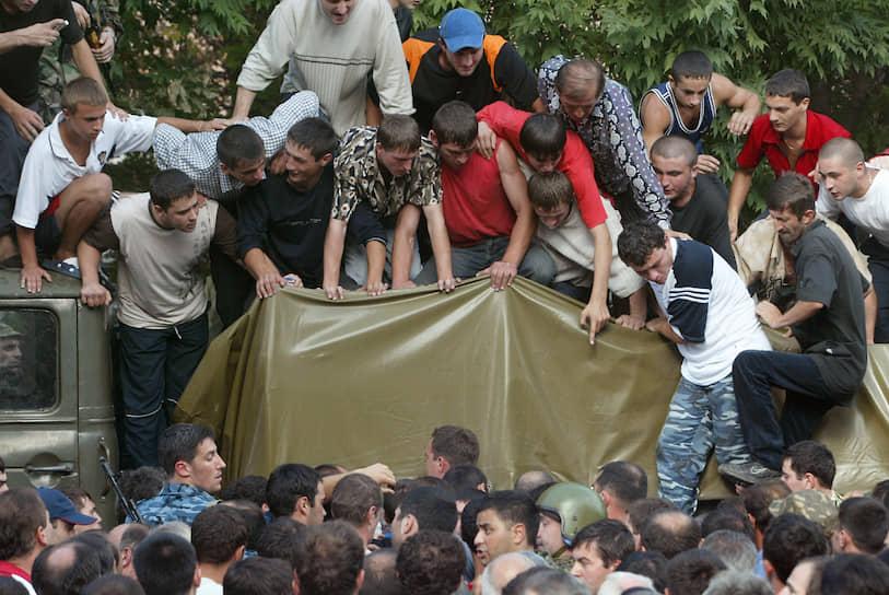 Люди, бегущие к школе, останавливались, падали на землю и прятались за деревьями. Из узкой калитки дома  передавали детей. Они были раздетые и окровавленные. Детей укладывали на носилки. Носилок было мало, и кто-то кричал в рацию, что нужны еще — и много