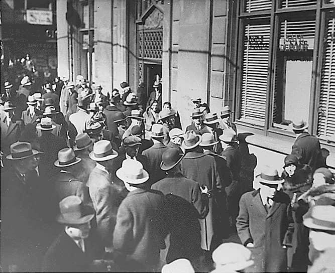 Тяжелее всего кризис проявился в США. Правительство бездействовало, если не считать принятого в 1930 году закона Смута-Хоули, в результате которого были введены высокие таможенные пошлины, что позволило кризису распространиться в Европу. Вкладчики массово изымали средства из банков, это привело к банкротству банков <br>На фото: люди занимают очередь в попытке забрать свои вклады в банке