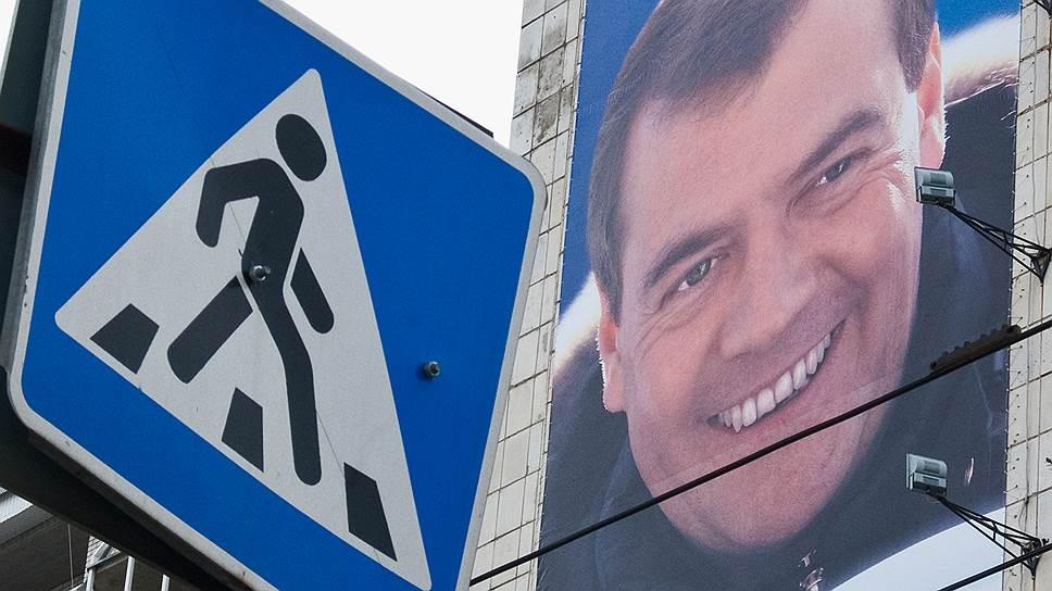 Премьер Дмитрий Медведев (изображен на плакате) подписал постановления правительства РФ, меняющие правила для водителей и пешеходов