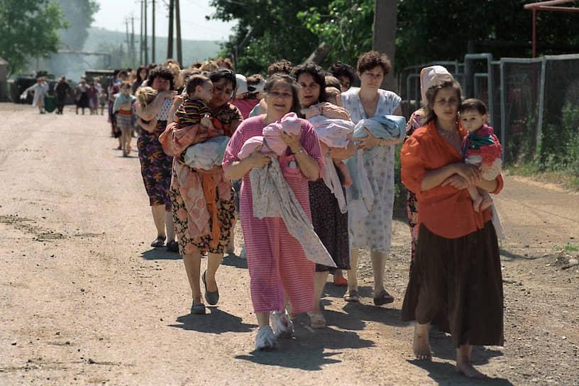 1995 год. Освобожденные заложники, в основном женщины и дети, покидают в сопровождении военных больницу в Буденновске, где они удерживались чеченскими террористами Шамиля Басаева