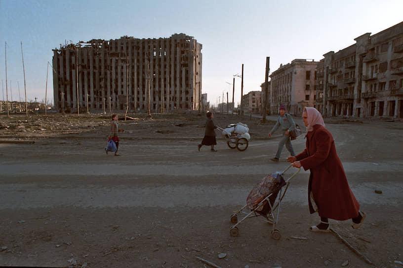 1995 год. Местные жители везут свои вещи на тележках по площади города