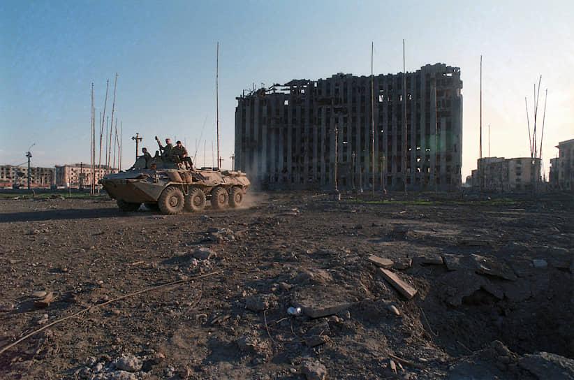1995 год. Солдаты на БТР в центре города на фоне разрушенного в ходе массированных бомбежек Грозного здания