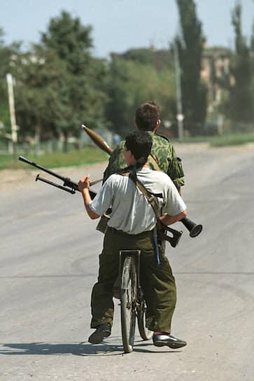 1995 год. Вооруженные чеченские дети едут на велосипеде по улице города
