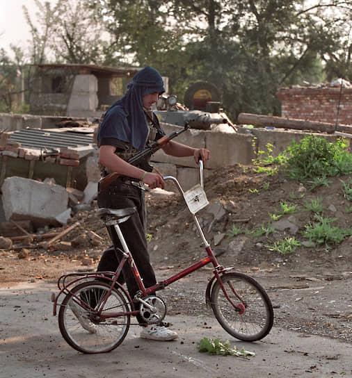 1995 год.  Вооруженный автоматом чеченский боевик на велосипеде на улице города