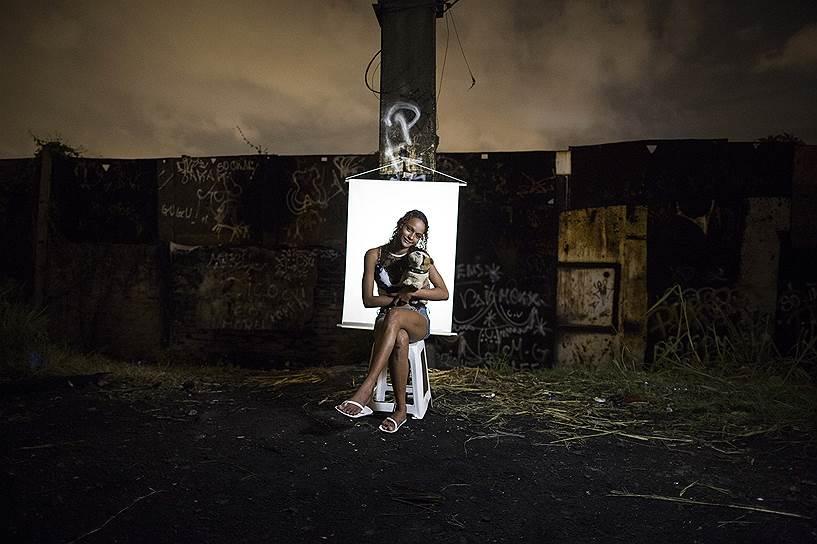 Не так давно торговля наркотиками во многих трущобах Рио прекратилась. Наркоторговцы заявляли об остановке бизнеса как минимум на два года, потому что «из-за распространения крэка и других подобных препаратов ситуация в общинах дестабилизируется, что еще сильнее затрудняет контроль над ними». Число крэклендов сегодня значительно сократилось. <br>На фото: Кетелин Сильва, 17 лет. Сильва — мать двоих детей — держит в руках игрушку, принадлежащую ее младшему сыну (старший ребенок — трехлетняя девочка), который родился недоношенным и сейчас находится в больнице   <br>