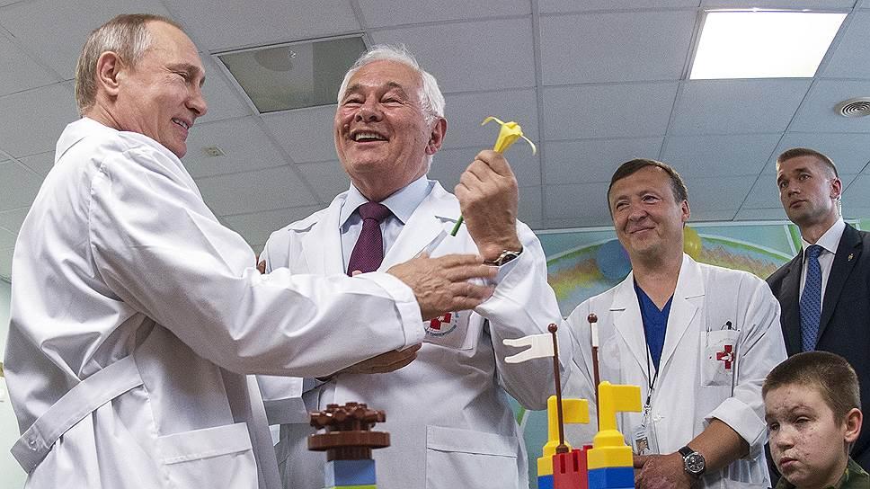 Президент России Владимир Путин (слева) и директор НИИ неотложной детской хирургии и травматологии Леонид Рошаль (второй слева) во время посещения Научно-исследовательского института неотложной детской хирургии и травматологии