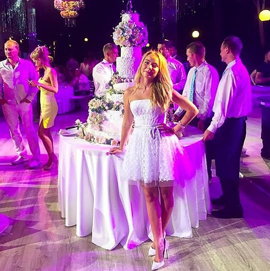Дочь невесты Александра Жулина позирует на фоне свадебного торта. Дети жениха не приехали на свадьбу отца