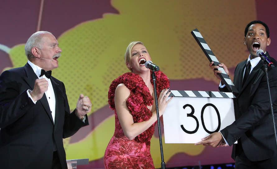 «Я живу довольно простой жизнью. Мне не приходится сниматься в высокобюджетных фильмах. У меня нет яхты или личного самолета, а посему мне никогда не придется волноваться о подобных вещах, если с ними что-нибудь случиться» <br>На фото: кинорежиссер Никита Михалков (слева) и голливудские звезды Шарлиз Терон и Уилл Смит на церемонии открытия Московского международного кинофестиваля