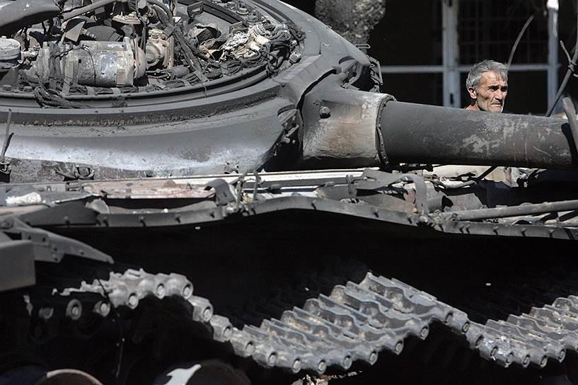Житель Цхинвала у сгоревшего грузинского танка