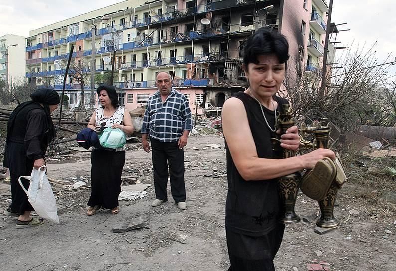 Местные жители во дворе своих разрушенных домов в городе Гори на востоке Грузии