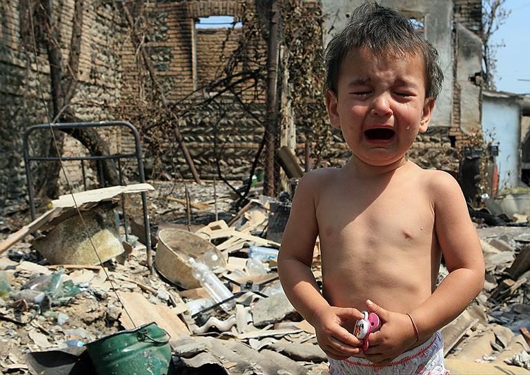 Плачущий ребенок у разрушенного дома в Цхинвале