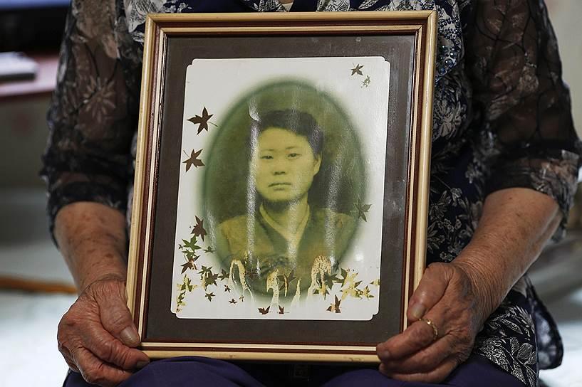 Ли Ок Сун показывает свою фотографию в одном из приютов для бывших секс-рабынь, который расположен в южнокорейском городе Кванджу. По словам женщины, она родилась в 1927 году в городе Пусан (Южная Корея) и в годы войны побывала во многих военных борделях. Снимок был сделан в 1947 году, через два года после капитуляции Японии, когда бывшая секс-рабыня пыталась получить гражданство в Китае. После окончания войны Ли не смогла вернуться в родной город, опасаясь слухов о своем прошлом. Она жила в Китае вплоть до 2001 года, после чего все-таки вернулась на родину