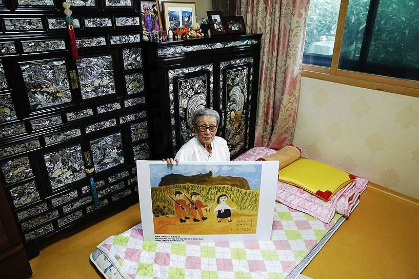 Жертва сексуального рабства 89-летняя Ким Бок Дон из Южной Кореи держит в руках одну из своих картин в приюте для бывших секс-рабынь. Согласно показаниям Ким, в возрасте 14 лет ее привезли на одну из «станций утешения», где принуждали обслуживать около 30 мужчин в сутки