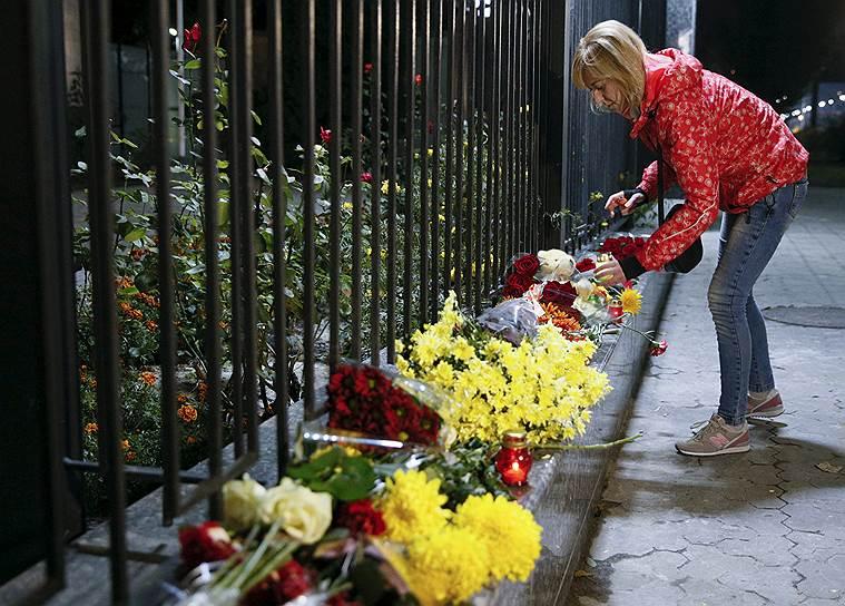 Люди несут цветы к Посольству России в Киеве