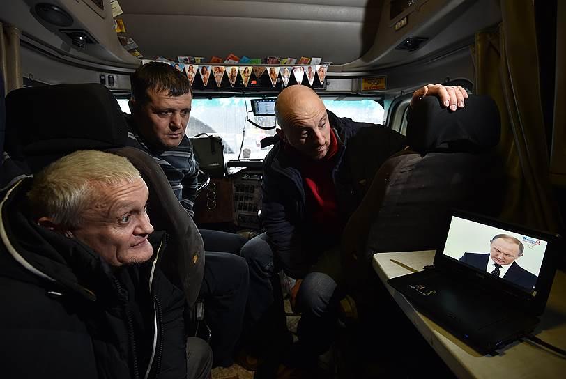 Участники акции дальнобойщиков «Платон» на трассе «Москва — Санкт-Петербург» смотрят в кабине грузового автомобиля ежегодное послание президента