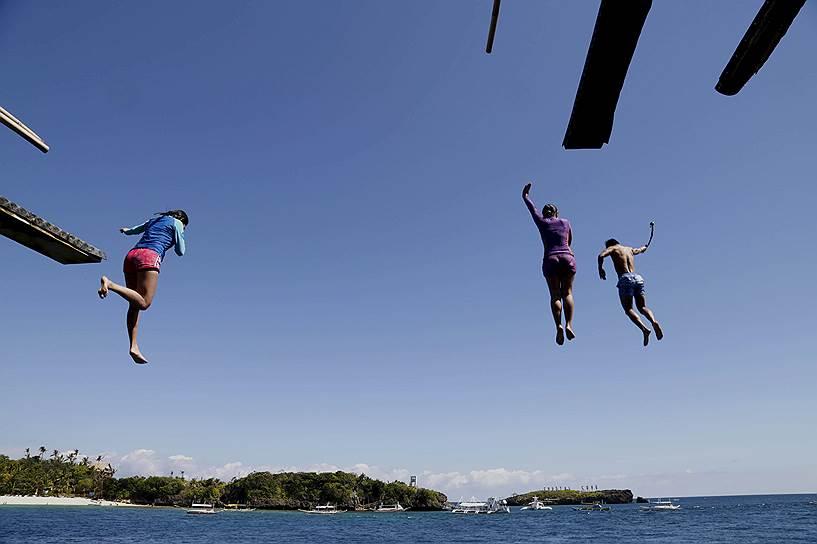 Остров Боракай, Филиппины. Туристы прыгают в море с 20-футовой скалы