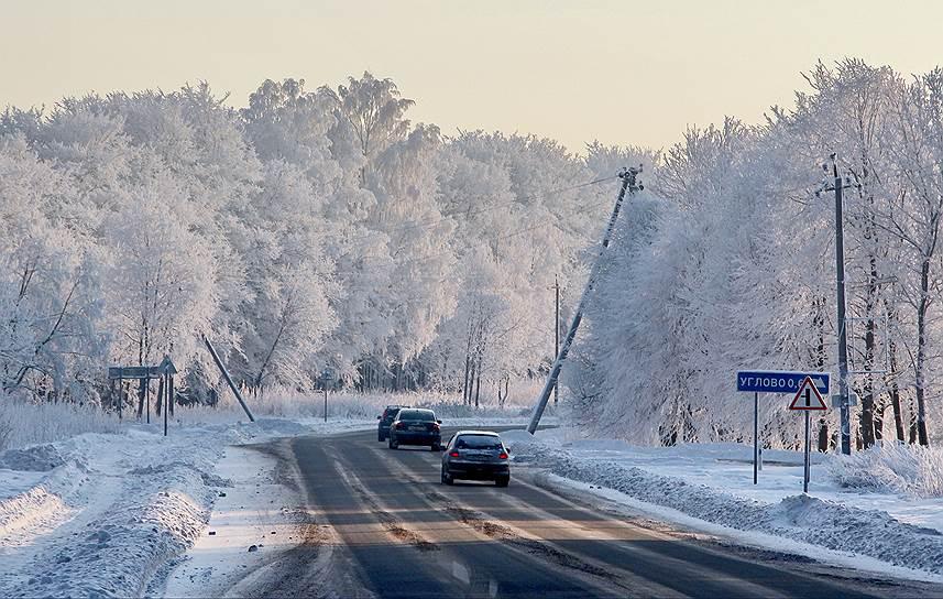 Россия, Ленинградская обл., Всеволожский р-он. Автомобили на зимней дороге в окружении заснеженных деревьев