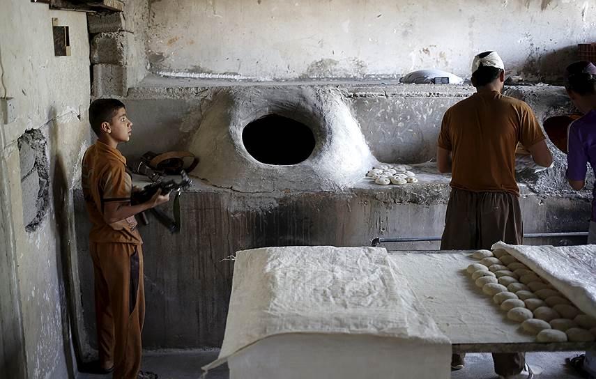 Туз-Хурмату, Ирак. Курдский мальчик с автоматом в местной пекарне