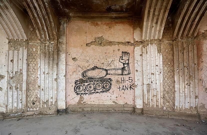 Исписанный граффити дворец, когда-то бывший домом королевской семьи, сейчас служит домом для бродячих собак, змей и скорпионов