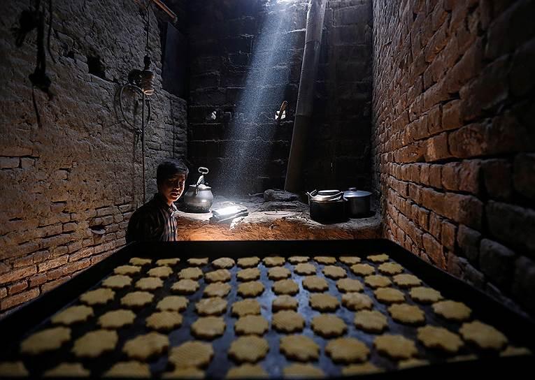 Кабул, Афганистан. Мужчина готовит традиционные сладости на фабрике к закят аль-фитра: милостыне, которую раздают всем нуждающимся мусульманам перед наступлением праздника Ураза-байрам