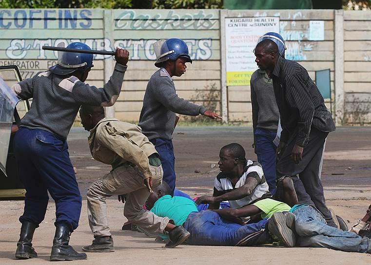 Хараре, Зимбабве. Полиция задерживает демонстрантов, после того как протест таксистов перерос в массовые беспорядки