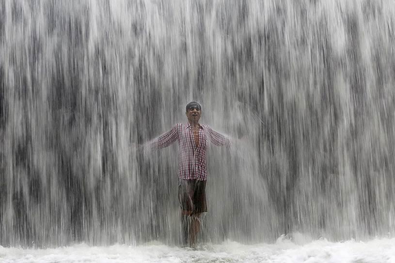 Мумбай, Индия. Мальчик стоит под потоком воды, переливающейся через плотину после сильного ливня