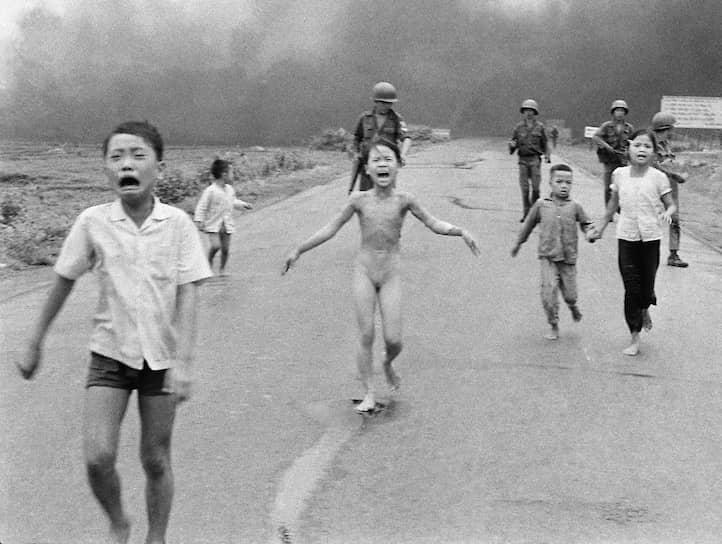 «Напалм во Вьетнаме», Ник Ут. 8 июня 1972 года.<br>В деревне Чангбанг к северо-западу от Сайгона шли ожесточенные бои между северовьетнамской и южновьетнамской армиями. Когда местные жители, среди которых и Ким Фук (в центре) покидали деревню, пилот южновьетнамских ВВС по ошибке принял эту группу за солдат и атаковал их напалмовыми бомбами. 9-летняя Ким Фук скинула с себя горящую одежду. Фотограф Ник Ут доставил пострадавших детей в госпиталь Кути. Врачи были уверены, что девочка не выживет. В последствии она получила мировую известность благодаря фотографии, переехала в Канаду и стала послом доброй воли ООН