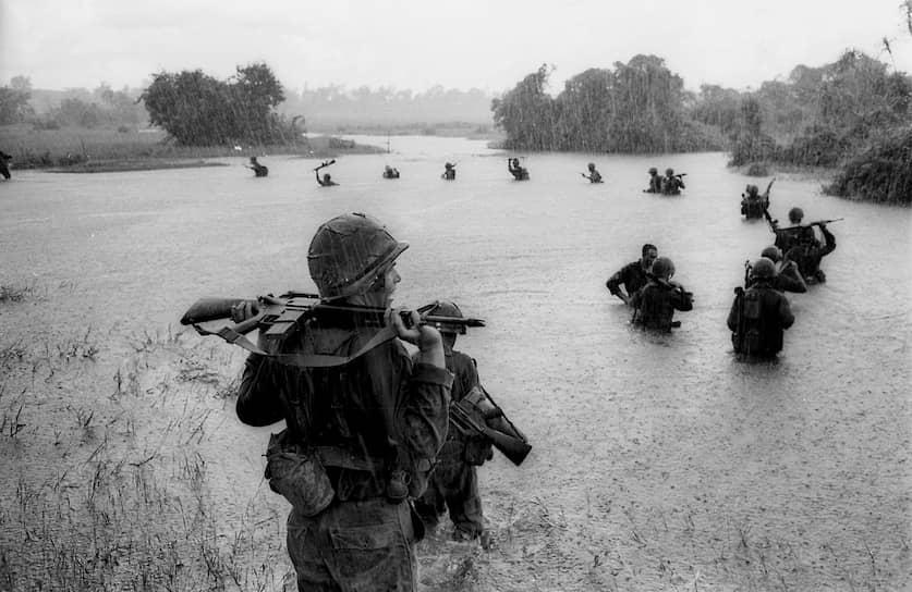 Генри Хьюет. 25 сентября 1965 года. «Американские десантники пересекают реку в поисках позиций северовьетнамских военных»<br> Вьетнамская война стала самым долгим конфликтом с участием войск США. Правительство страны потратило на военные действия $352 млрд