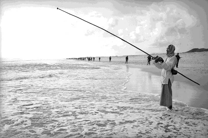 Эдди Адамс. 28 января 1966 года. «Вьетнамский рыбак на фоне американских пехотинцев»<br>Высадка военных из США в Куангнгай стала самой крупной передислокацией войск во Вьетнамской войне. Тогда 4 тыс. пехотинцев были выброшены на пляж, чтобы обнаружить расположение северовьетнамских военных