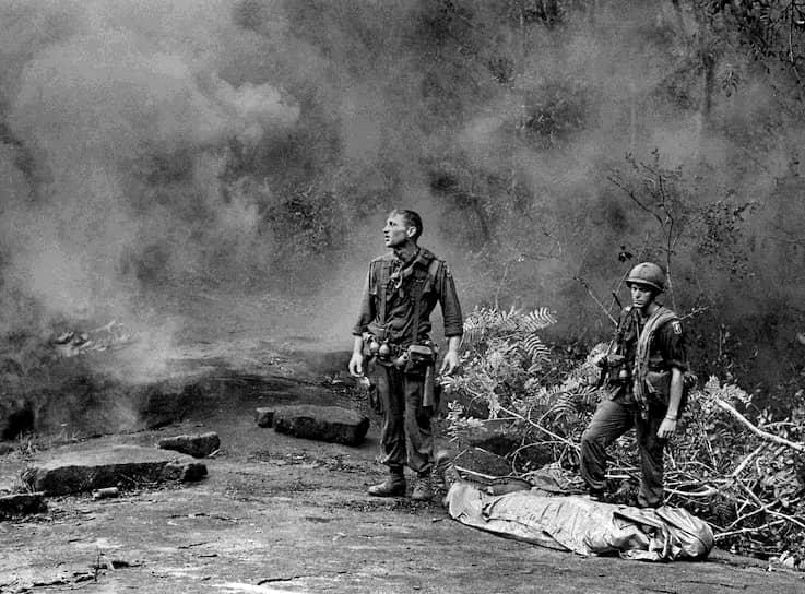 Пол Эпли. 1 октября 1966 года. «Американские военные в дыму ждут прибытия вертолета с медиками в джунглях»<br>В 1965-1966 годах американские военные совместно с южновьетнамской армией развернули масштабное наступление в джунглях Южного Вьетнама. При этом широко использовались зажигательные средства, химическое и биологическое оружие