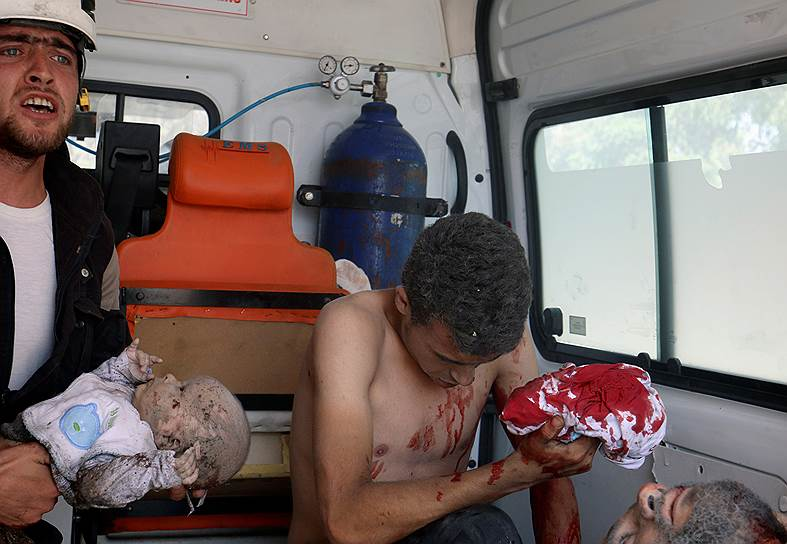 Член «Сирийской гражданской обороны» держит раненого младенца в машине скорой помощи после того, как ребенка вытащили из-под завалов в пригороде Алеппо