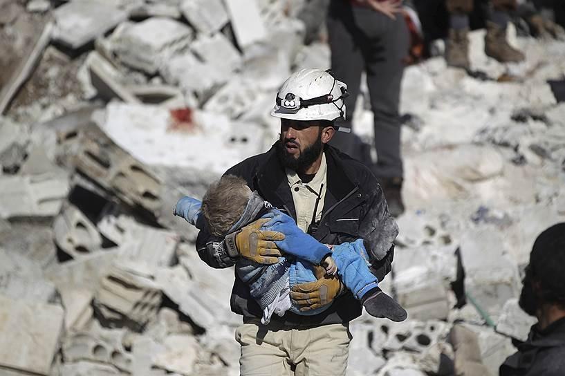 Волонтер несет мертвого ребенка, который погиб после авиударов по городу Мааррет-эн-Нууман в провинции Идлиб. «Белые каски» утверждают, что этот удар в январе 2016 года нанесли российские ВКС