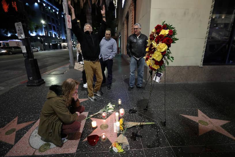 Поклонники актера несут цветы к его звезде на Аллее славы в Голливуде